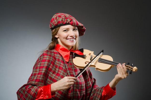 A mulher na roupa escocesa no conceito musical Foto Premium