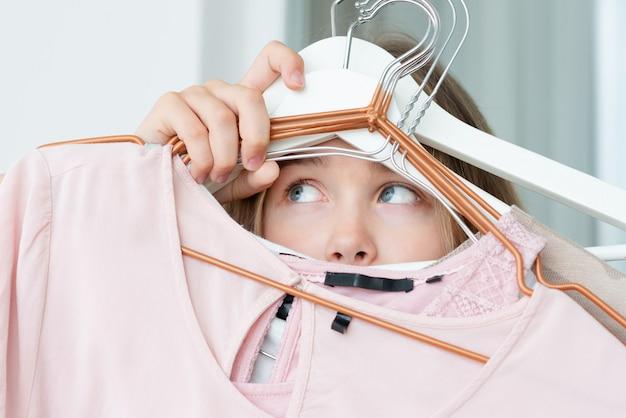 A mulher não pode escolher quais roupas levar para viajar. roupa, forma, estilo e conceito dos povos - mulher que escolhe o vestuário em casa. Foto Premium