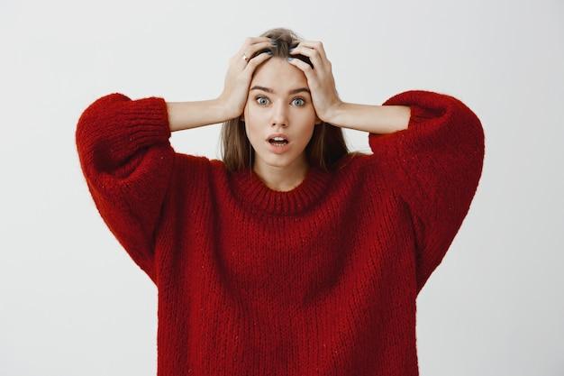 A mulher não sabia como resolver o problema, sentindo-se preocupada. salientou a mulher bonita chocada elegante suéter solto vermelho, segurando as mãos na cabeça, sentindo-se nervoso enfrentando problemas sobre parede cinza Foto gratuita