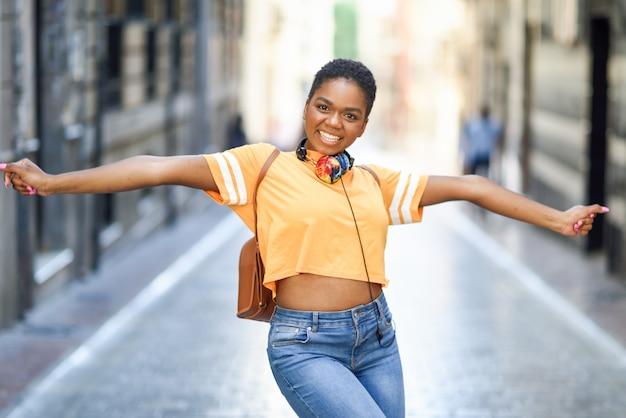 A mulher negra nova está dançando na rua no verão. menina viajando sozinha. Foto Premium