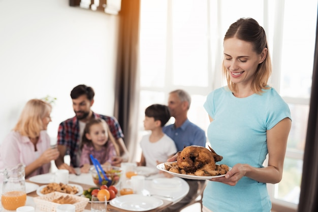 A mulher no t-shirt azul está estando no fundo com chiken. Foto Premium
