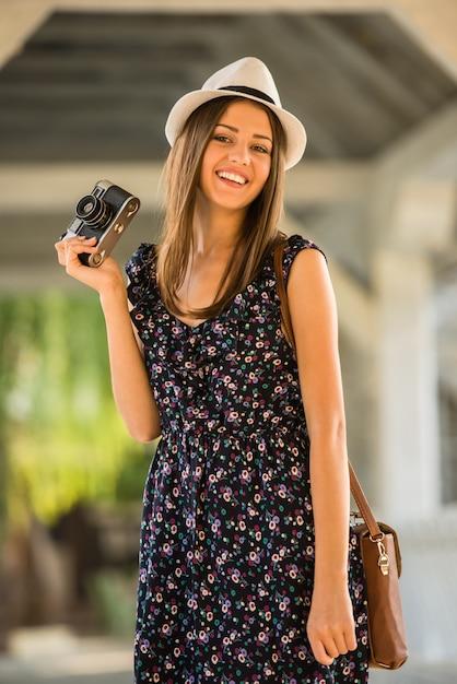 A mulher no vestido e no chapéu está guardando a câmera antiquado. Foto Premium
