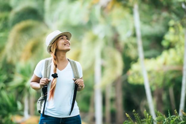 A mulher nova do turista com trouxa aprecia a natureza que olha afastado. Foto gratuita