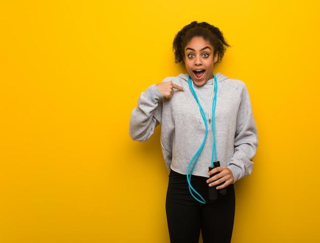 A mulher preta nova da aptidão surpreendida, sente bem sucedida e próspera. segurando uma corda de pular. Foto Premium