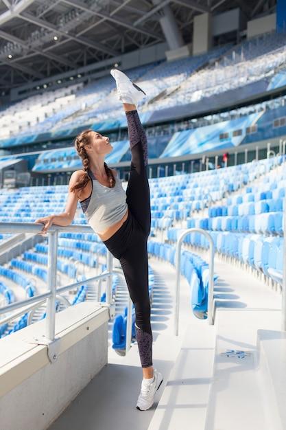 A mulher puxa a perna para cima no estádio. Foto Premium