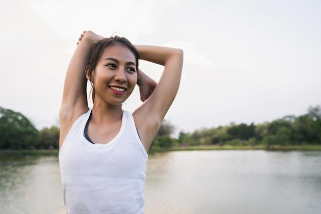 A mulher saudável do corredor asiático novo aquece o corpo que estica antes do exercício e da ioga Foto gratuita