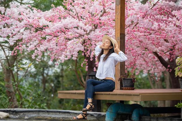 A mulher sentada debaixo da cerejeira Foto gratuita