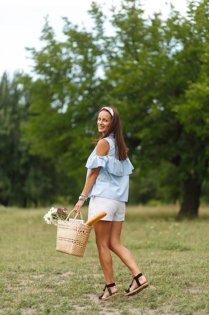 A mulher smilling nova bonita dentro com as flores na cesta de vime anda no parque verde do verão. Foto Premium