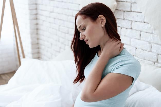 A mulher tem um pescoço dolorido. ela se sente mal. uma careta no rosto dele. Foto Premium