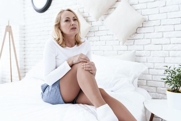 A mulher tem uma dor no joelho, ela está fazendo uma massagem Foto Premium