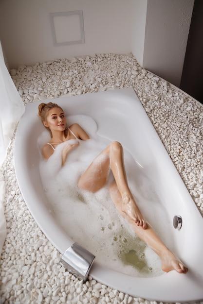 A mulher toma banho com espuma pela manhã. jacuzzi Foto Premium