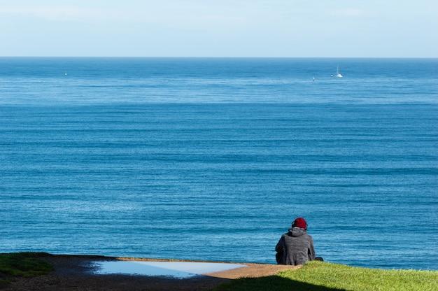 A música de escuta do homem novo está sentando-se na borda do penhasco do mar. Foto Premium