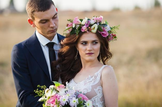 A noiva e o noivo andam ao pôr do sol. Foto Premium