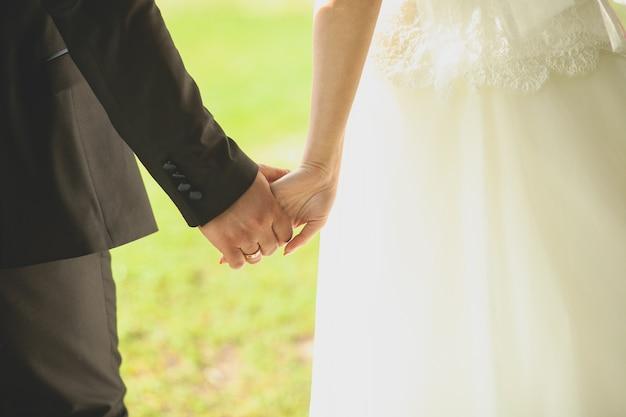 A noiva e o noivo dão as mãos e andam. Foto Premium