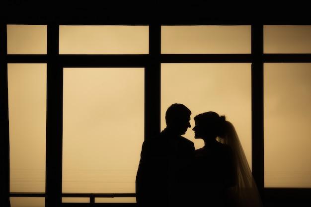 A noiva e o noivo estão perto da janela. Foto Premium