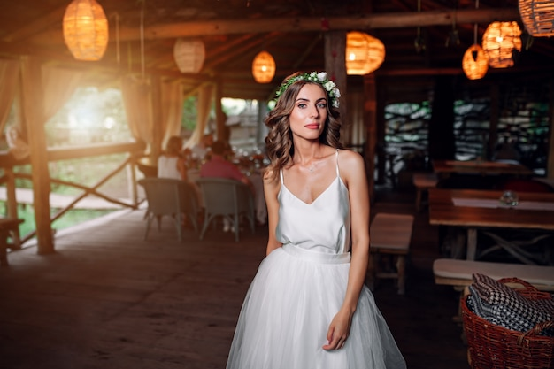 A noiva em um vestido branco e uma coroa de flores está no restaurante Foto Premium