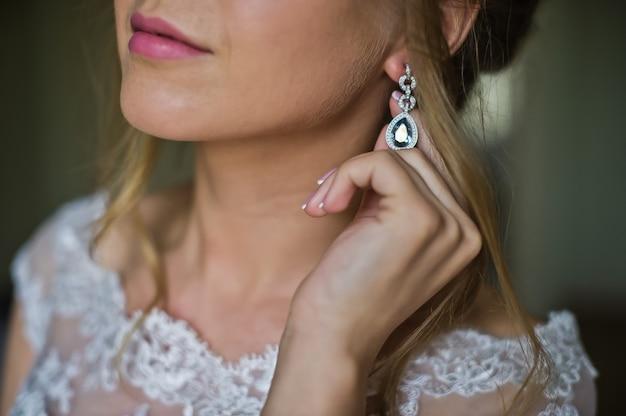 A noiva em um vestido de noiva usa brincos Foto Premium