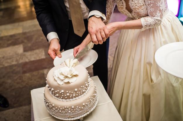 A noiva eo noivo cortar o bolo de casamento em um banquete em um restaurante Foto Premium
