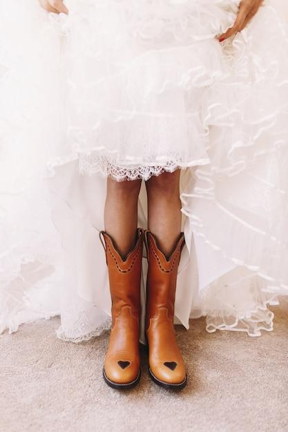 A noiva ergue a saia para mostrar as botas debaixo dela Foto gratuita