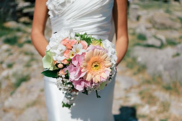 A noiva está segurando um buquê de flores frescas de primavera e verão em tons pastel em um fundo desfocado, foco seletivo Foto Premium