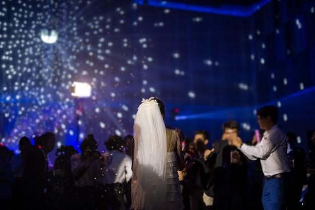 A noiva feliz dança primeiramente no banquete de casamento com convidados e cor conduziu a iluminação. Foto Premium
