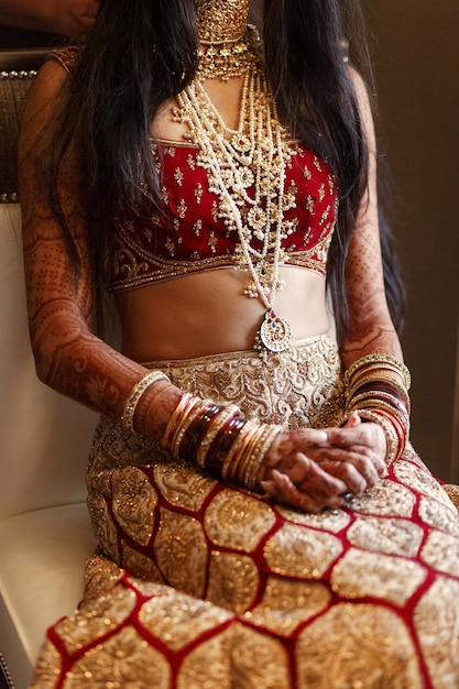 A noiva indiana com um lindo traje vermelho fica na cadeira branca Foto gratuita