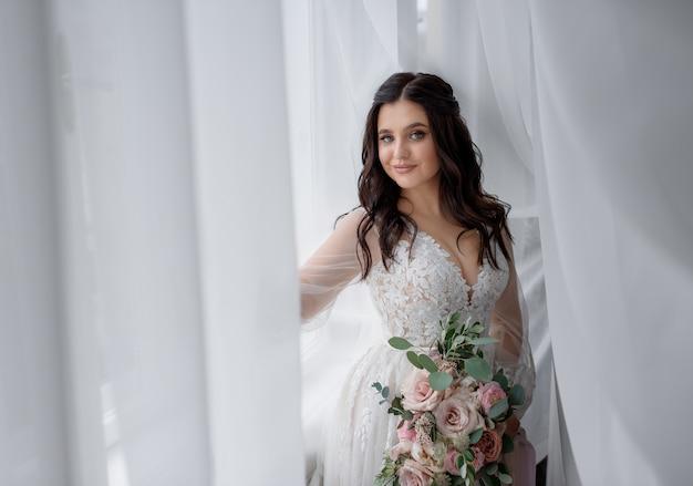 A noiva morena muito sorrida está segurando o buquê de casamento perto da janela e olhando direto Foto gratuita