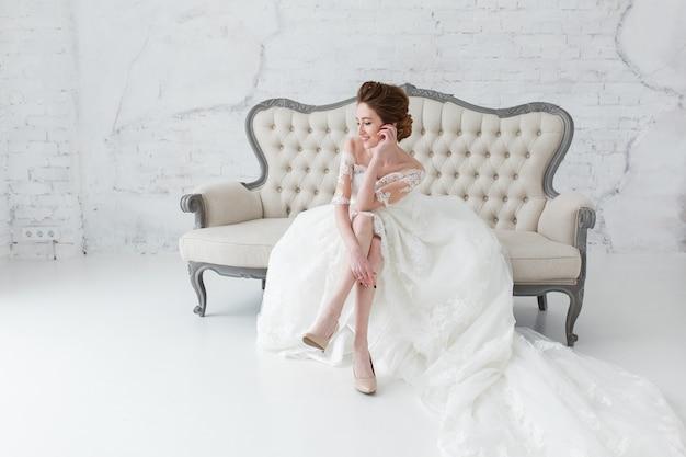 A noiva no vestido longo que senta-se no sofá dentro no interior branco do estúdio gosta em casa. Foto gratuita