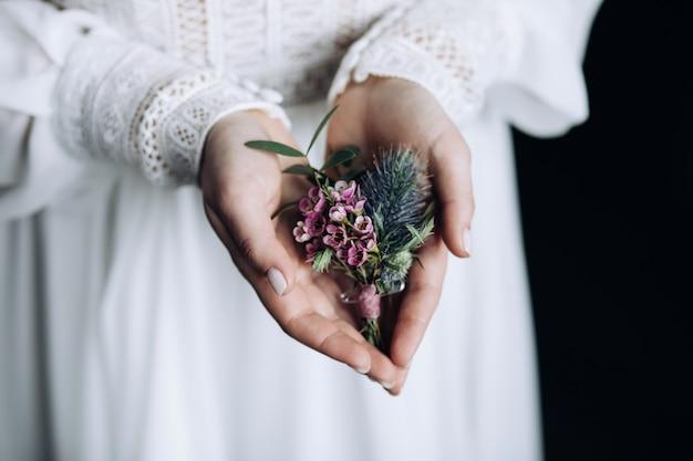 A noiva segura uma flor na lapela de flores cor de rosa nas palmas das mãos Foto Premium