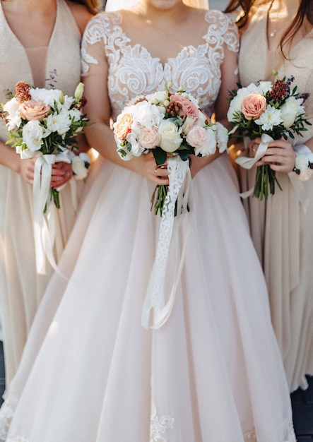 A noiva tem um buquê de casamento nas mãos dela Foto Premium