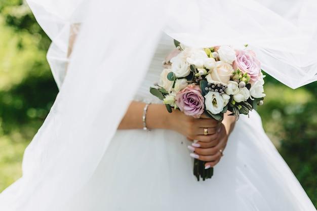 A noiva tem um buquê de casamento nas mãos Foto gratuita