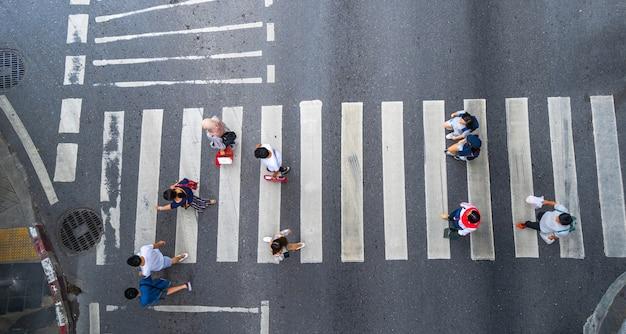 A opinião superior da foto aérea das pessoas anda na rua na cidade sobre a estrada do tráfego da passagem pedestre Foto Premium