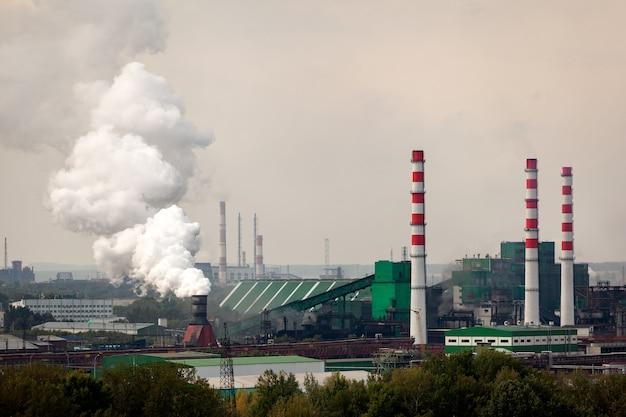 A paisagem de uma enorme cidade industrial, com fábricas e guindastes altos, de onde saem enormes nuvens de fumaça. poluição do meio ambiente por plantas e indústrias Foto Premium