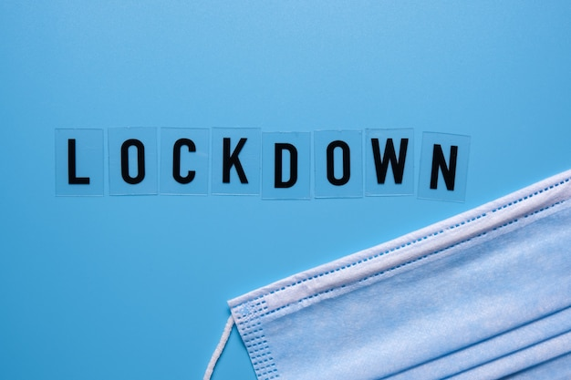 A palavra lockdown e uma máscara médica sobre um fundo azul. segunda onda covid 19. Foto Premium