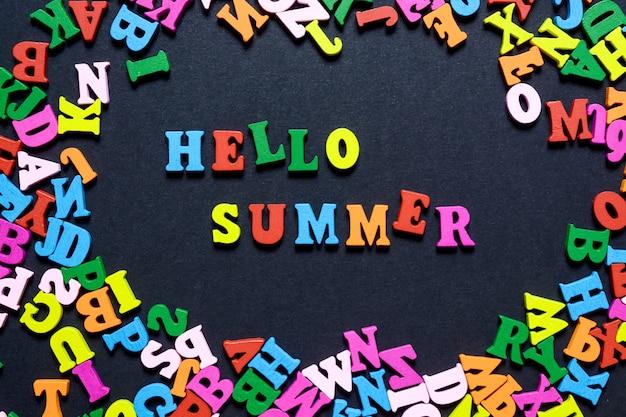 A palavra olá no verão de letras de madeira multi-coloridas em um fundo preto Foto Premium