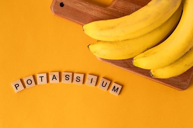 A palavra potássio é colocada em blocos de madeira no meio de bananas em um fundo amarelo Foto Premium