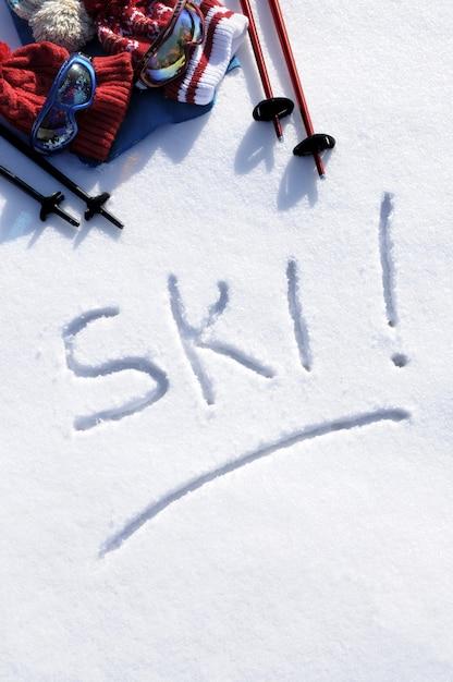 A palavra ski escrita na neve com bastões de esqui Foto gratuita