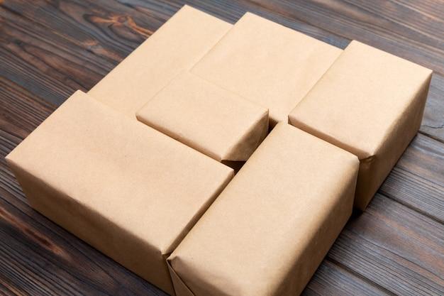 A parcela do pacote do pacote do correio de brown para você projeta. caixa de papelão sobre um fundo escuro de madeira Foto Premium