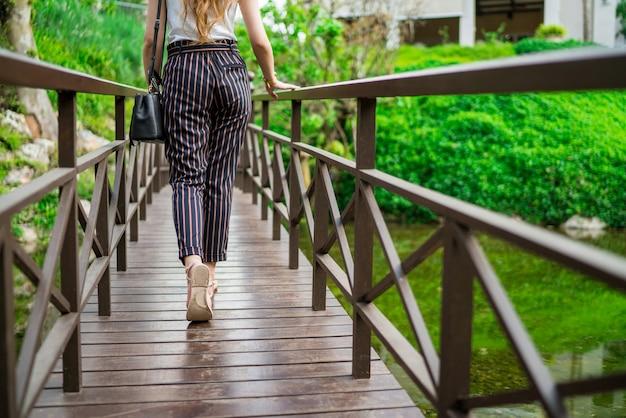 A parte de trás da mulher andando na ponte de madeira Foto Premium