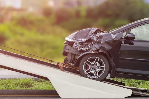 A parte dianteira do carro preto obtém danificada acidentalmente na estrada. Foto Premium