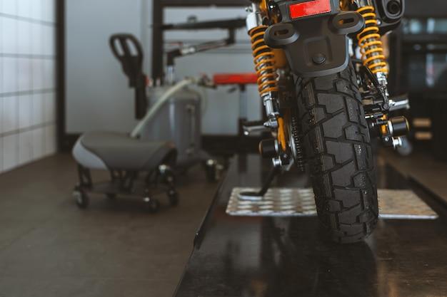 A parte traseira das motocicletas clássicas em pé na oficina Foto Premium