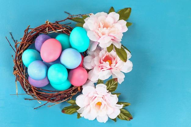 A páscoa coloriu os ovos coloridos que encontram-se dentro do ninho ao lado das flores em um fundo azul. Foto Premium