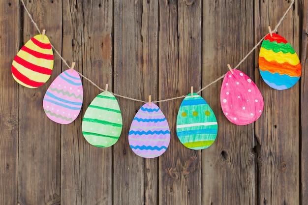 A páscoa de papel pintou os ovos pintados pendura em prendedores de roupa na parede de madeira velha do fundo. Foto Premium