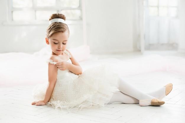 A pequena bailarina com tutu branco na aula de balé Foto gratuita