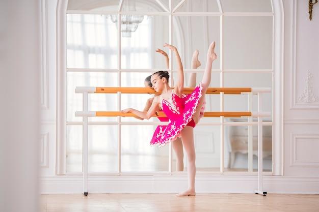 A pequena bailarina com um tutu rosa brilhante está envolvida em uma barra de balé em frente a um espelho em um belo grande salão branco Foto Premium