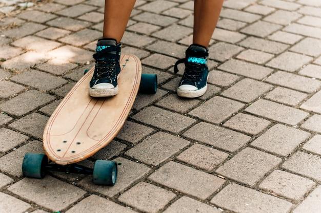 A perna da menina nas sapatilhas que estão em um skate. Foto Premium