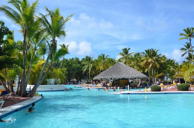 A piscina luxuosa bonita em um recurso tropical, pessoa relaxa no hotel. Foto Premium