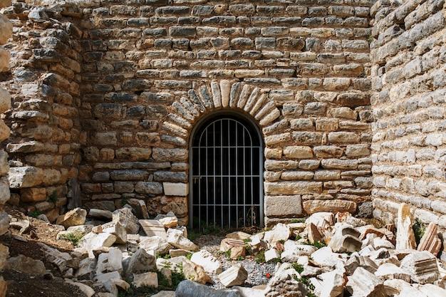 A porta é da grade de metal de um antigo edifício antigo, um castelo de pedra com enormes blocos. Foto Premium