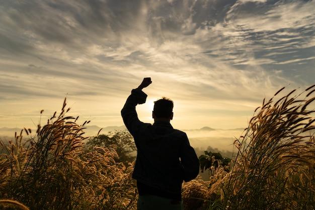 A posição feliz do homem da silhueta com mãos aumenta na montanha com céu do nascer do sol. Foto Premium