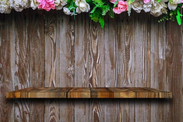 A prateleira de madeira fica nas pranchas de madeira velhas, com rosas decoradas em cima. Foto Premium